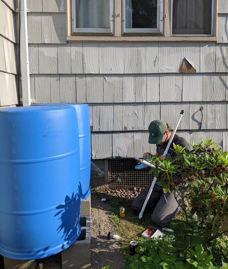 man Install a BlueBarrel Rainwater Catchment System
